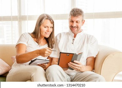 Husband and wife on a couch in their apartment with a tablet and a notepad