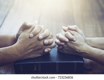 husband and wife  are praying together over holy bible on wooden table with the light from above with  copy space for your text