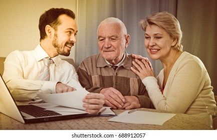 Husband and wife preparing agreement papers with social worker at home