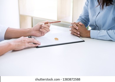 Husband and wife are reading divorce agreement and filing pen to signing decree of divorce (dissolution or cancellation) of marriage filing divorce papers and two golden marry ring.