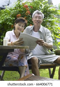 husband and wife reading newspaper in the garden