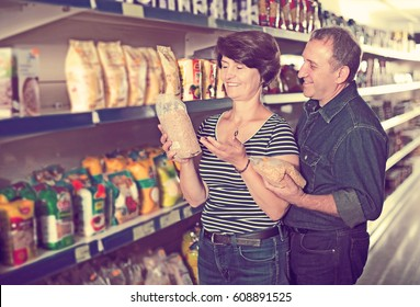 Husband and wife selecting a groats at the grocery store