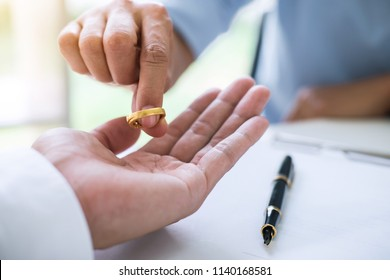 Husband and wife are signing decree of divorce (dissolution or cancellation) of marriage filing divorce papers and returning wedding ring.