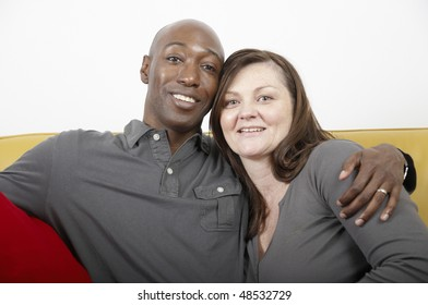 Husband and wife sit together in a hug
