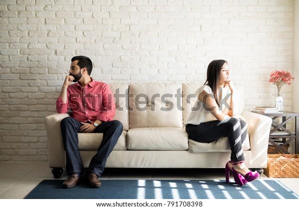 夫と妻がソファに座り、家で口論して話をしない