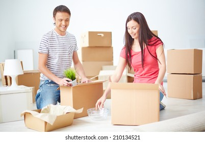 Husband and wife sitting on the floor of new flat and unpacking boxes