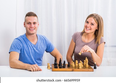 Husband and wife sitting at the table and playing chess.Leisure time for happy couple