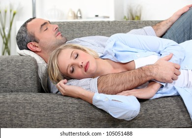Husband and wife sleeping on their couch