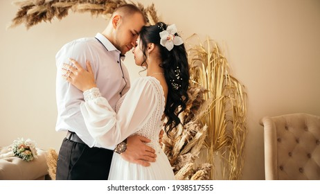 Husband and wife smiling happy couple hugging at the photo session studio. Wedding married bride and groom celebrate their engagement. Procreation romantic amazing lovers newlyweds indoor copy space