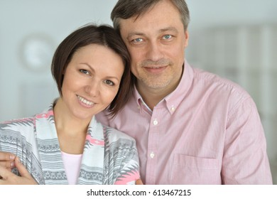 husband and wife spend time together on a gray background