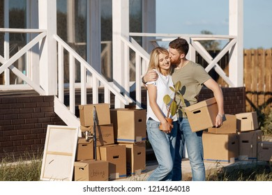 Husband and wife standing in front of new buying home with boxes. bought first home
