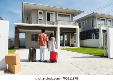 Husband and wife standing in front of new buying home with luggage and  boxes. Happy Asian married male and female couple move to modern house. Family lifestyle new life. They bought first home