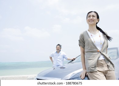 husband and wife standing on car side