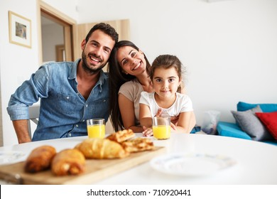 Husband and wife with they little daughter sitting at the kitchen table.Family portrait.