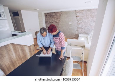 Husband and wife use a laptop to arrange a new apartment