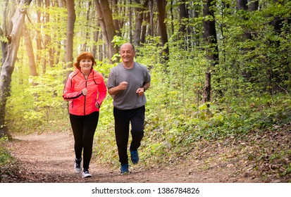 Husband and wife wearing sportswear and running in forest at mountain