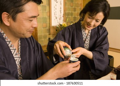 husband and wife in yukata pouring out alcohol drink