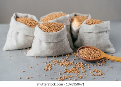 Husbandry concept. Raw buckwheat in sacks, wooden spoon near, splited cereals, isolated over grey background. Roasted groats or grains