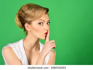 Hush. Charming woman having secret holds finger on lips, shows shh sign. Attractive woman in white dress, retro hairdo making gesture silence. Discount, sale, season sales. Copy space for advertise.