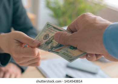 Hush money and corruption in business concept, close up of male hand giving hundred US dollar bill to female business person