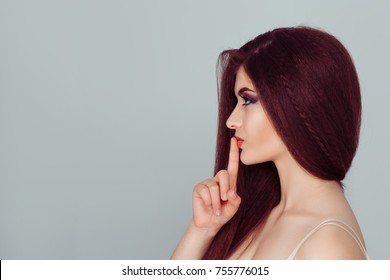 Hush. Side view Young woman in profile smiling asking for silence or secrecy with finger on lips shh hand gesture light green. Young woman with dark long hair keeping her forefinger by lips