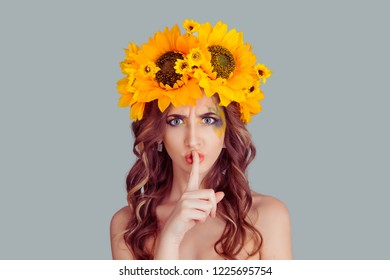 Hush. Woman with floral headband wide eyed asking for silence, secrecy, finger on lips shh hand gesture gray background wall. Fashion girl with crown from sunflowers on head isolated gray background.