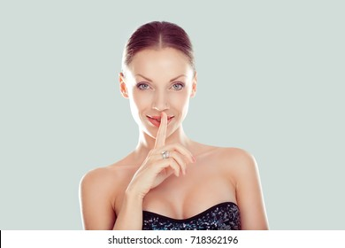 Hush. Woman smiling wide eyed asking for silence or secrecy with finger on lips shh hand gesture light green background. Pretty girl placing fingers on lips shhh sign symbol. Positive face expression