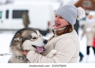 Husky dog hugs with adult woman. Winter outdoor walking - Reshetiha, Russia - 02.02.2019