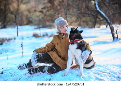 Husky kissing a boy in the snow at a winter park