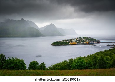 Husoy fishing village on the Senja Island in Norway with mountains in the background. The village covers the entire island of Husoy which is located in the Oyfjorden at the northwest coast of Senja.