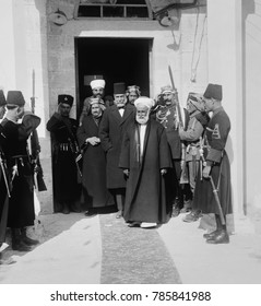 Hussein bin Ali, Sharif of Mecca, leads a group from a doorway, in Amman, Trans-Jordan, 1921. Two of his sons, Abdullah and Faisal, became the Emirs of British Mandates, Trans-Jordan and Iraq