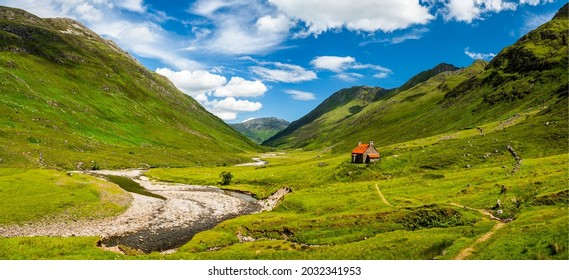 A hut in a mountain valley. Mountain cabin in mountain valley. Mountain panoramic landscape