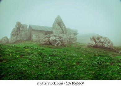 A hut in the mountains on a green meadow, surrounded by some big rocks and cloaked in the mist. Recorded in Germany.