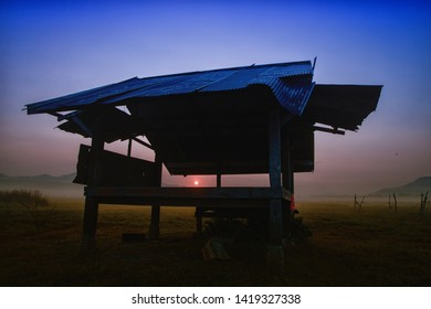 Hut on empty grassland with fog in the morning