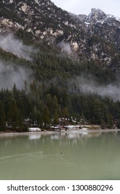 Hut on the lake in the mountains. A lonely place in the Alps in winter. The first snow at the foot of the mountain.