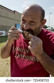 Hutchinson, Kansas. USA, 18th September, 2015Man eating bacon wrapped chicken lollipop at the Kansas State Fair.