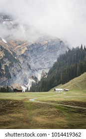 huts in the high valley of Bargis near Flims on a cloudy day in the spring