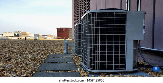 HVAC AC compressor Coil outside installation with fan and radiator and protective mech. Installed Coil on roof with rocks attached to coil lines and near concrete tiles on roof