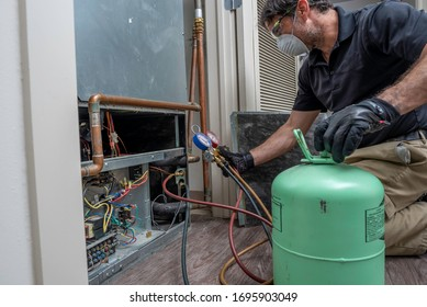 HVAC contractor wearing a mask and safety glasses while charging a heat pump air conditioner