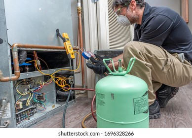 HVAC contractor wearing PPE, servicing a heat pump