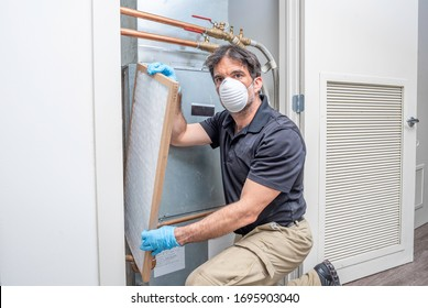 HVAC contractror wearing a medical face mask, replacing a air filter inside a home