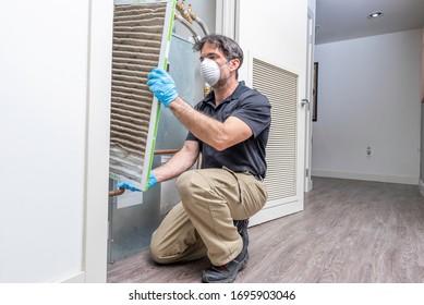 Hvac maintenance technician removing a diry air filter from a heat pump