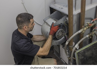 Hvac tech installing a blower motor into a water based heat pump