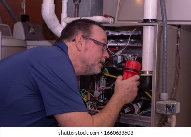 HVAC Tech Looking Over A Gas Furnace  Blue Shirt