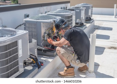 Hvac tech on roof top checking a condenser unit, with condensers in the back ground.