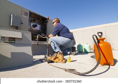 HVAC Tech on Roof top working on Cooling System
