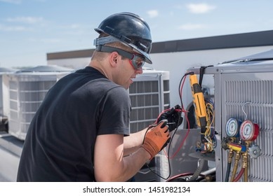 Hvac Tech standing outside on a roof top next to some air conditioner condensers