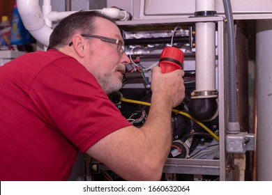 HVAC Technician Checking Out A High Efficiency Furnace  Red Shirt