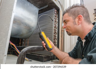An Hvac technician searching for a refrigerant leak on an evaporator coil.