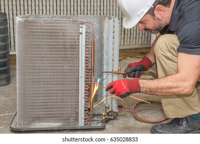 HVAC technician soldering a copper joint on a condensing coil.